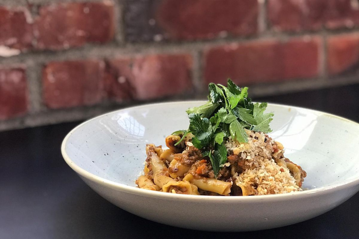 A dish of mushroom bolognese at Maslow's with a brick wall in the background.