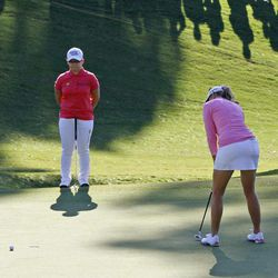 Jiyai Shin, of South Korea, left, watches as Paula Creamer misses a par putt on the 16th hole during the ninth playoff hole of the Kingsmill Championship LPGA Tour golf tournament in Williamsburg, Va., Monday, Sept. 10, 2012.  Shin won the tournament.