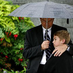 Michael Hanson and his son Reese, both of Portland, Ore., find shelter under an umbrella as they wait in line to get into the priesthood session of conference on a rainy Saturday.