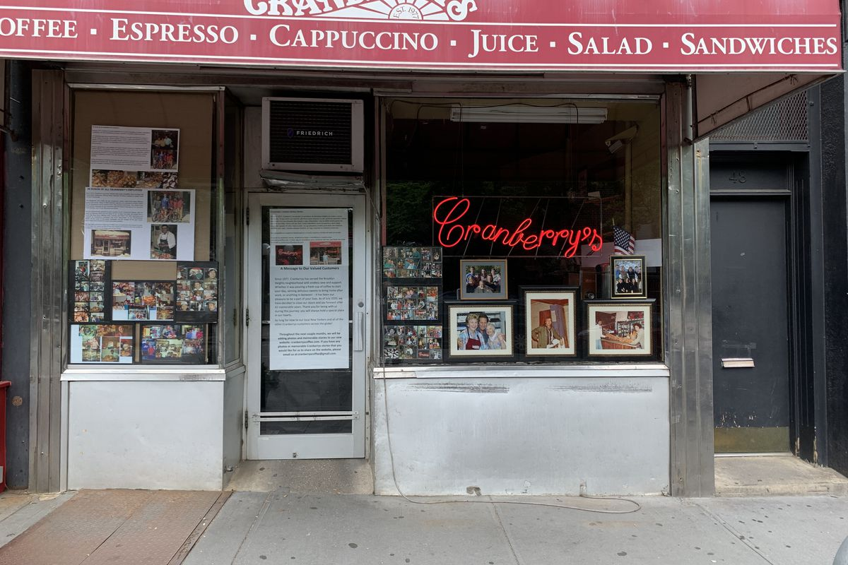 The exterior of a shop with a red awning, and a neon red sign that reads cranberry's