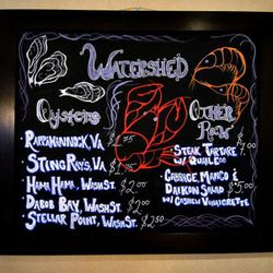 The raw bar menu written on chalkboard