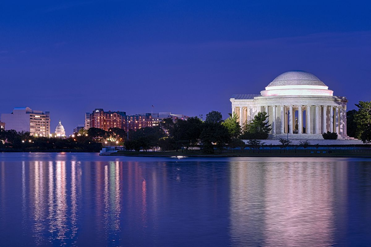 The Tidal Basin and Jefferson Memorial at night. The water gleams from street lights and the U.S. Capitol can be seen in the background.