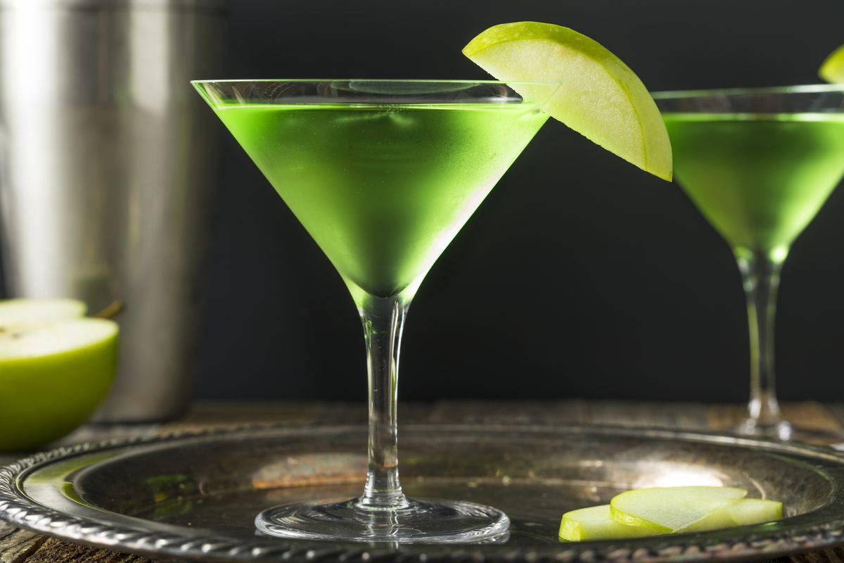 Appletini cocktail in a martini glass sits on a metal tray; apple garnish on the glass rim.