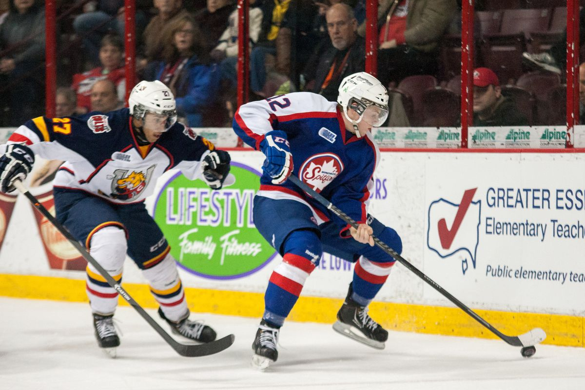 Ben Johnson #12 of the Windsor Spitfires moves the puck against Cordell James #27 the Barrie Colts on February 27, 2014 at the WFCU Centre in Windsor, Ontario, Canada.