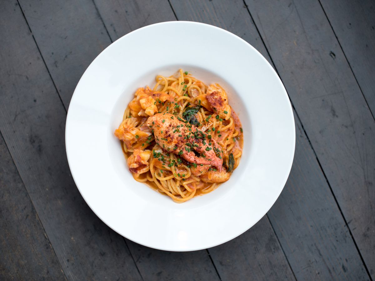 A white bowl with red dressed noodles studded with hunks of lobster on a wood table background