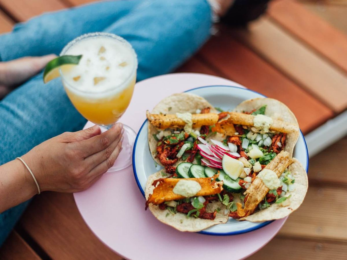A plate of four overlapping tacos sit on a bright pink side table beside a wooden lounge chair where a woman rests with a cocktail in her hand