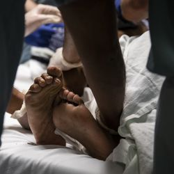A man suffering from a stab wound curls his toes as he writhes in pain in the Emergency Department at Mount Sinai Hospital, Tuesday evening, Sept. 10, 2019.