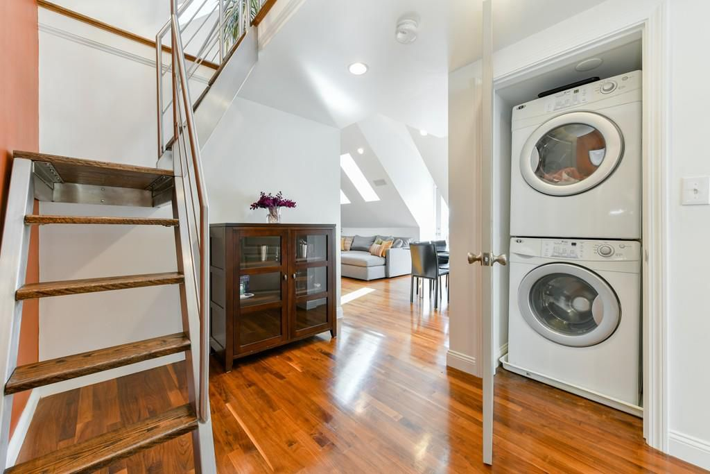 The bottom of some stairs with a stacked washer-dryer across from it and an open living room just beyond.