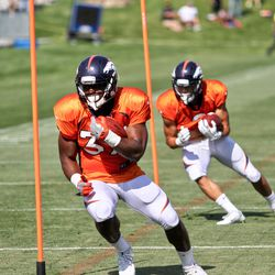 Broncos rookie RBs Royce Freeman (front) and Phillip Lindsay (back) work their way through the poll drill at training camp.