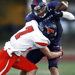 Mountain Crest's #7 Kaden Lindley, left, tackles Woods Cross' #8 Marcus Tueller as they play Friday, Aug. 31, 2012.