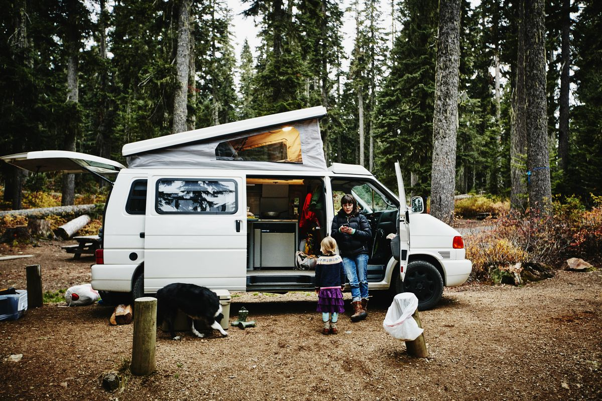 A family parks a camping van in the woods.