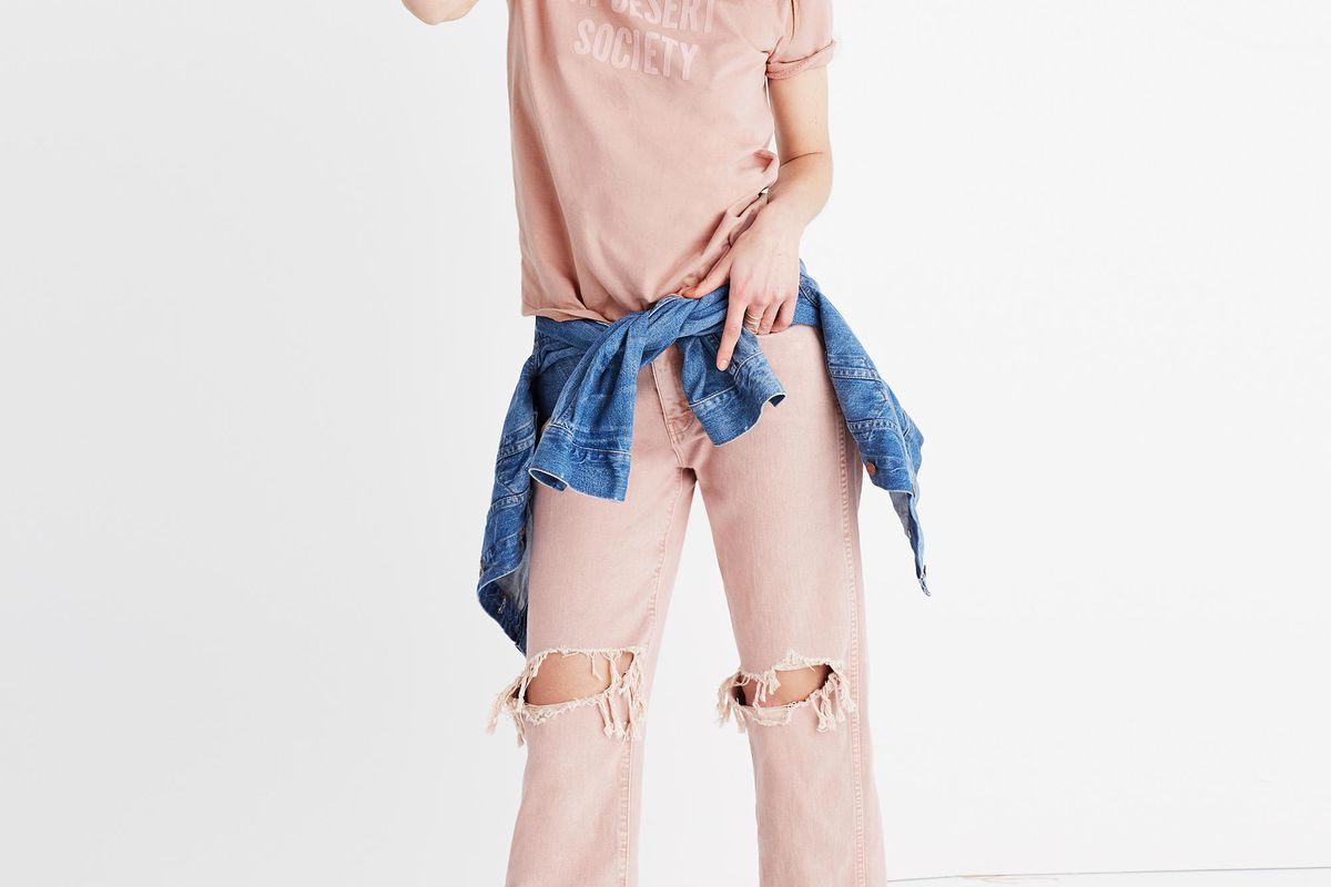 A model wearing pink jeans, a pink tee shirt, and blue shirt tied around her waist