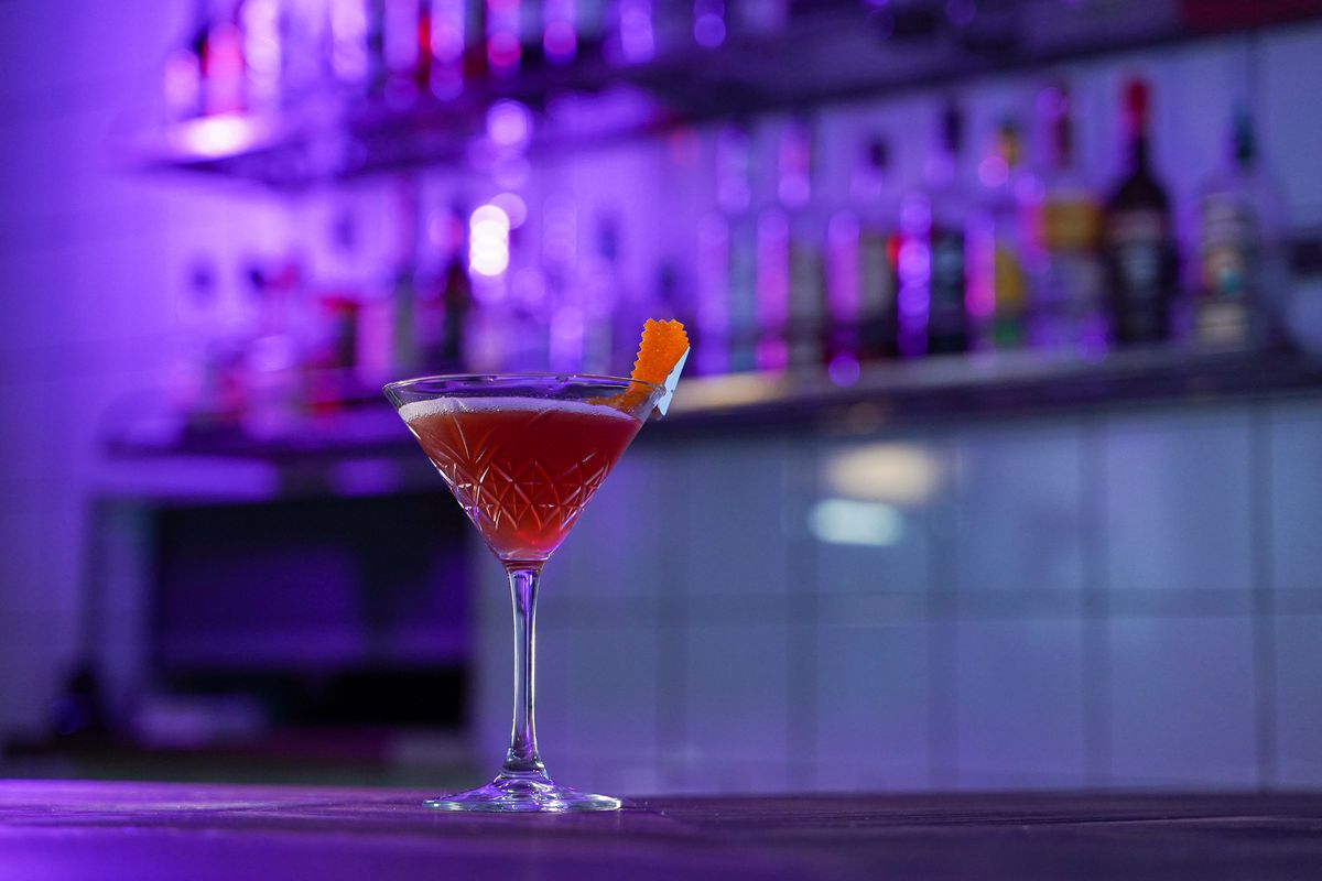 A cocktail glass sits on a counter with a purple bar backdrop