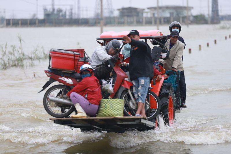 Les résidents sont transportés sur un chariot élévateur vers la terre ferme à travers les eaux de crue provoquées par les fortes pluies du typhon Vamco après son arrivée sur terre dans la province de Thua Thien Hue le 15 novembre 2020.
