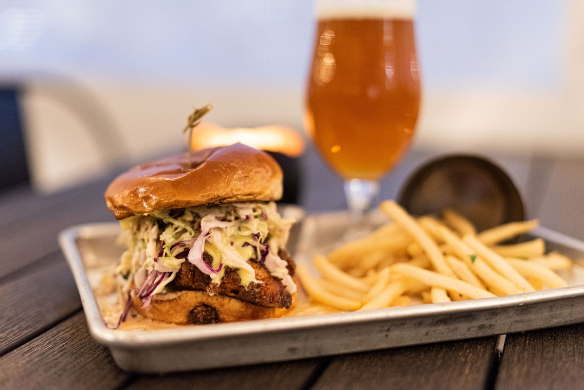 Hot chicken sandwich, fries, and a craft beer at Newhall Refinery.