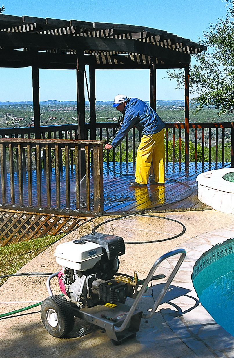<p><strong>3. Rinse</strong> Working from the railings down, use the power washer to spray away any loosened grime and wood pulp. Hold the tip at least 18 inches from the wood surface, but this time align the fan with the gaps in the deck. This enables you to dislodge any debris between the boards. Rinse two or three times to ensure that there's no debris to interfere with the bleach or the finish. Also, wet nearby foliage to protect it from the bleach used in the next step.</p>