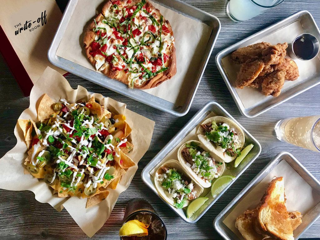 A table full of bar snacks from pizzas to nachos.