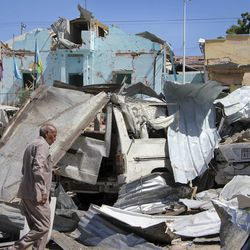 A Somali police officer walks through the destruction at the scene of a car bomb attack in Mogadishu, Somalia Tuesday, June 20, 2017. A number of people are dead after a suicide car bomber in a vehicle posing as a milk delivery van detonated at a district headquarters in Somalia's capital, police said Tuesday.