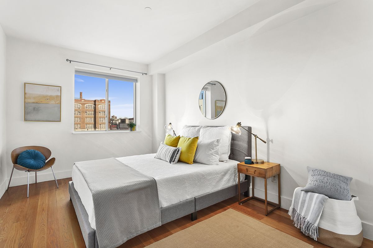 A bedroom with white walls and wood floors overlooks the street.