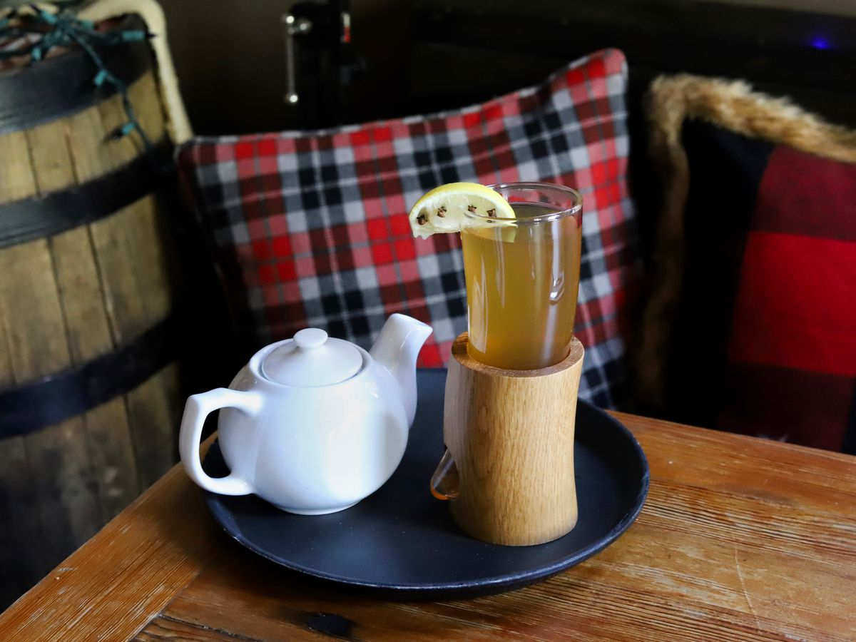 A hot cocktail is served in a glass drinking horn, which is perched in a wooden holder. A white teapot sits next to it on a tray on a wooden table. A barrel and plaid pillows are visible in the background.