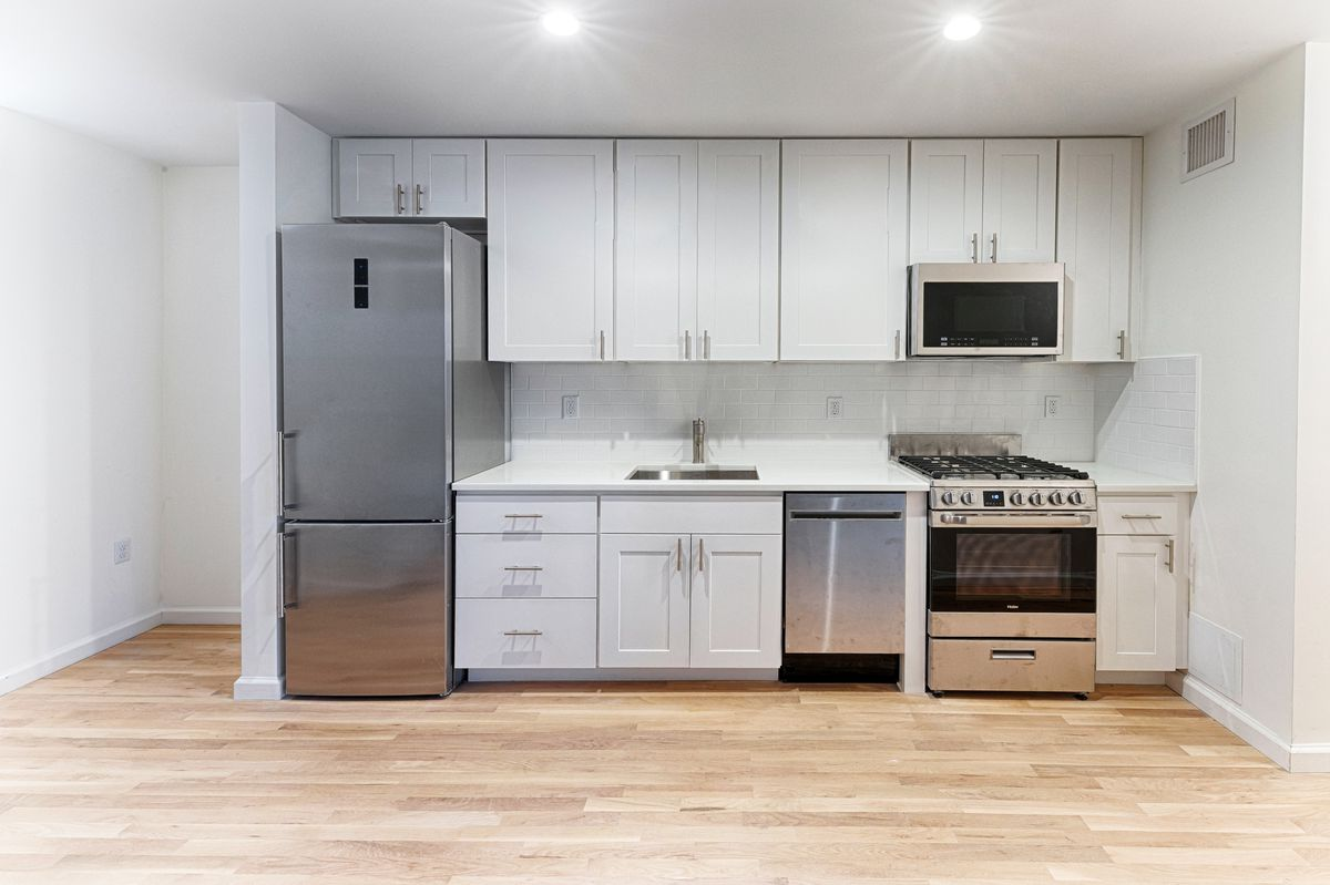 A kitchen with hardwood floors and white cabinetry.