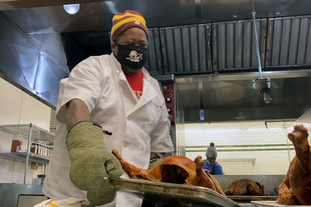 Chef Phil Jones wears a beanie and a mask while lifting a turkey out of the oven and onto a metal table.