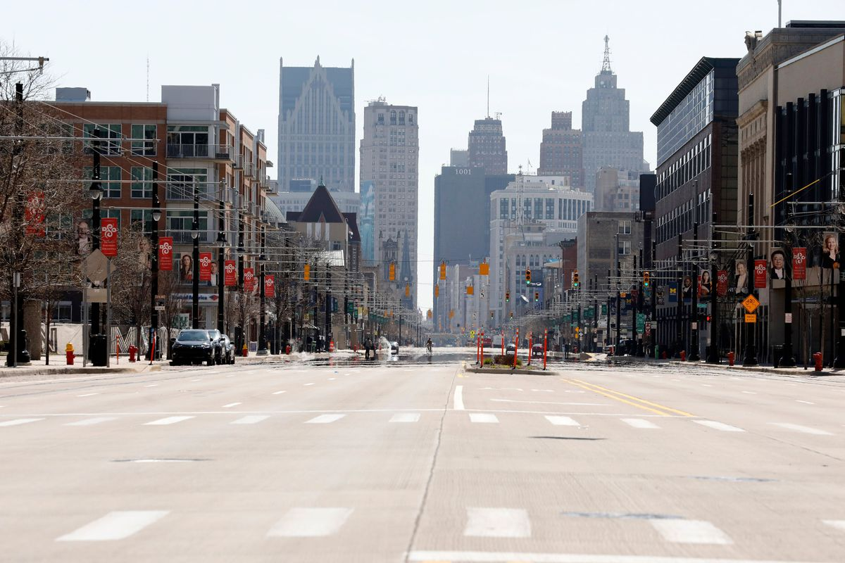 An empty, wide boulevard. Buildings line the street on either side and skyscrapers are seen in the distance.
