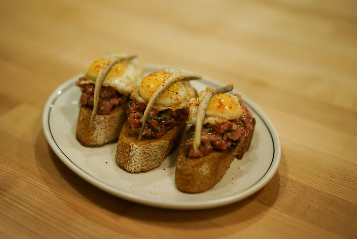 Three pieces of toast with steak tartare, a fried qual egg, and an anchovy each, on a white plate.