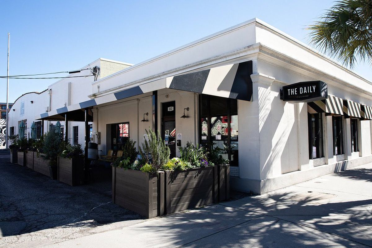 The bright white exterior of the Daily coffee shop and cafe in gleams on a sunny, blue sky day in Charleston, SC