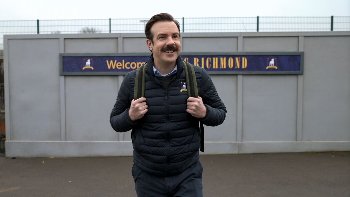 """Ted Lasso stands holding his backpack straps on his shoulders in front of a sign that reads in part """"Welcome Richmond."""""""