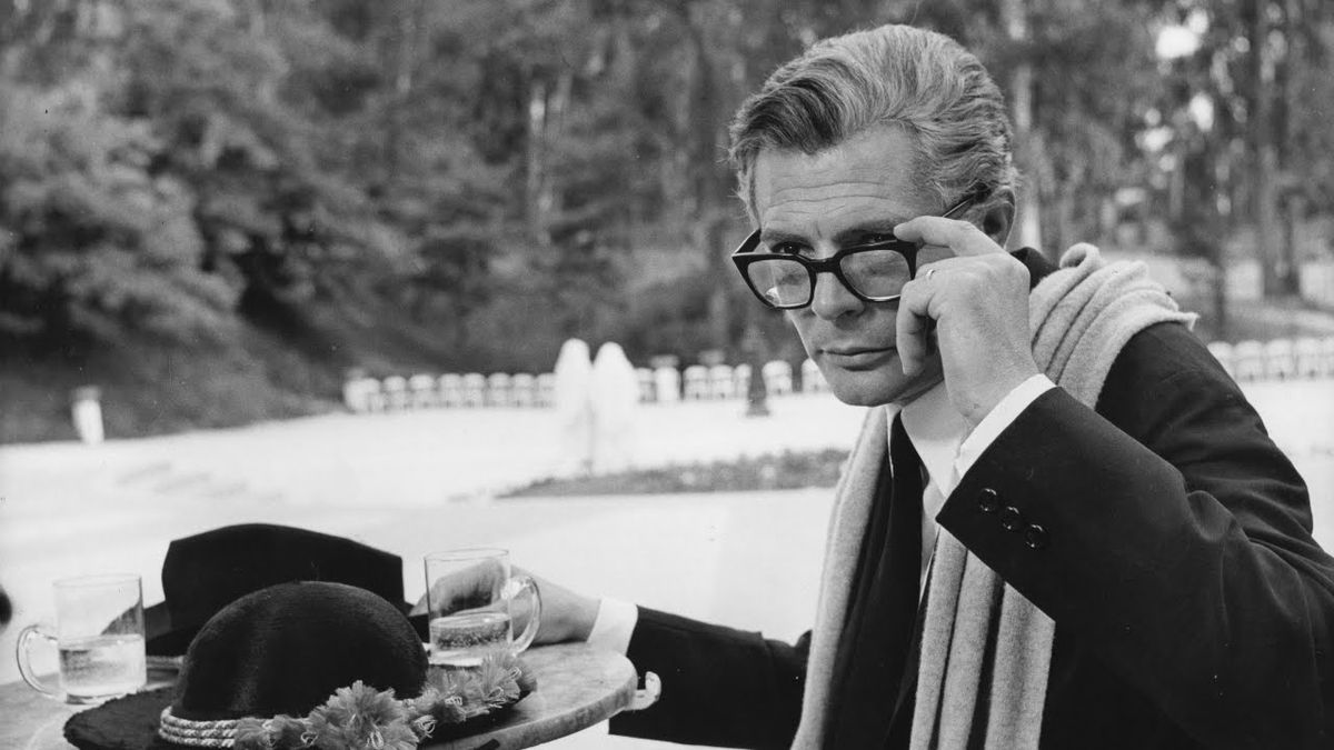 Marcello Mastroianni as Guido Anselmi peers over his glasses to scrutinize something off-screen