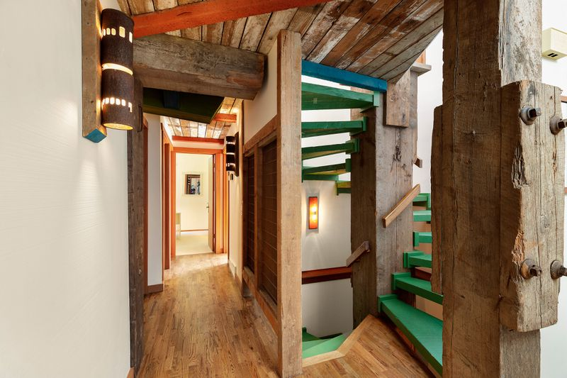 A hallway and spiral staircase has bright green stairs, exposed beams, and wood floors,