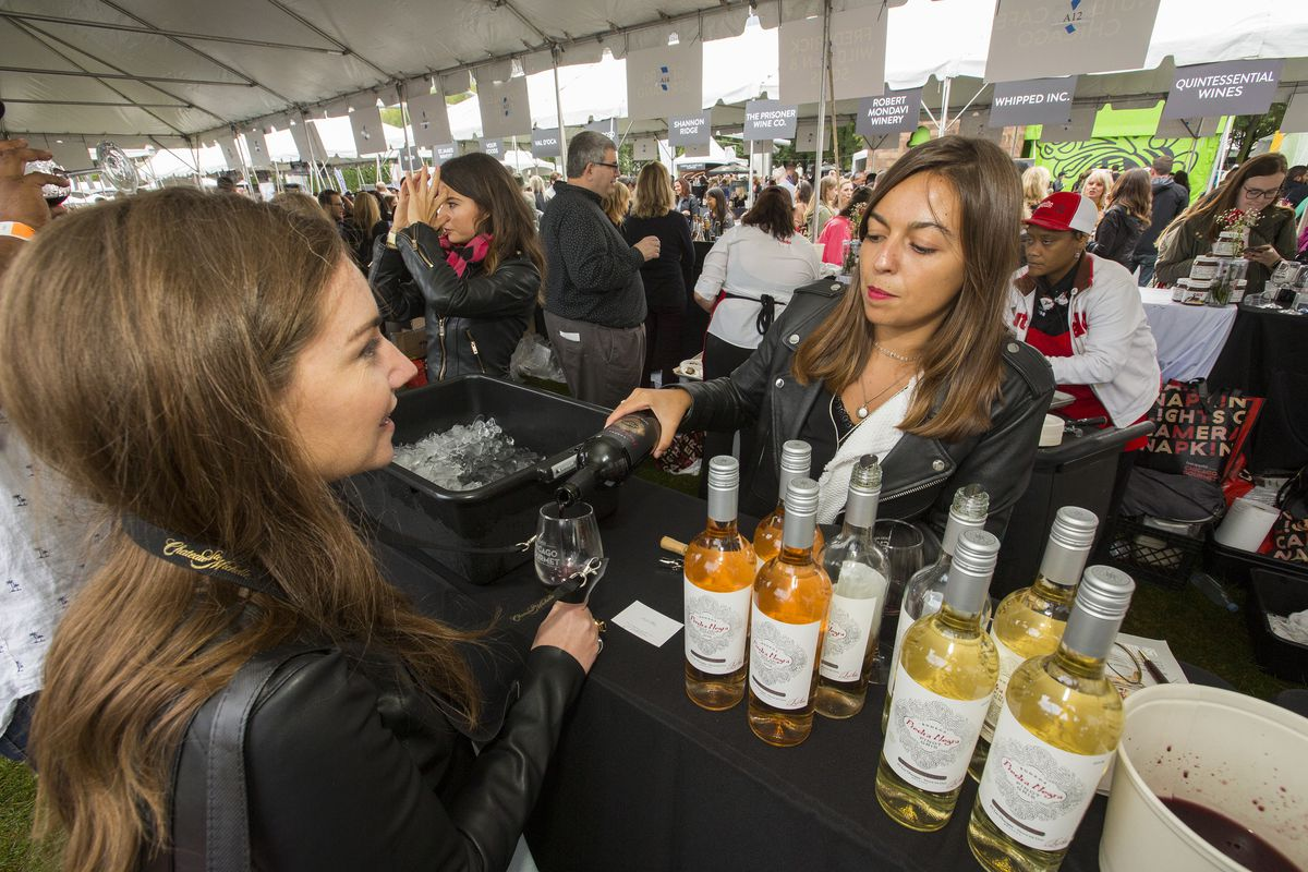 A woman pours a glass of wine for a Chicago Gourmet attendee.