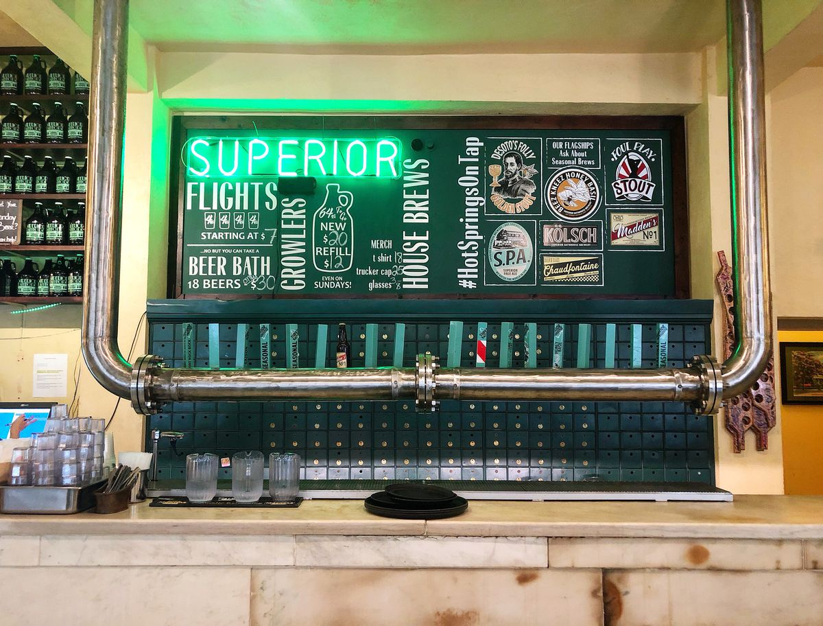 a neon sign and menu over a lineup of beer taps.