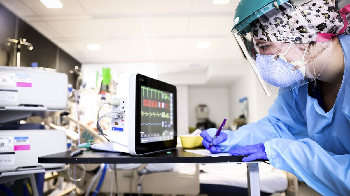 A health care worker in gown, mask, and face shield leans on a desk and looks at a monitor.