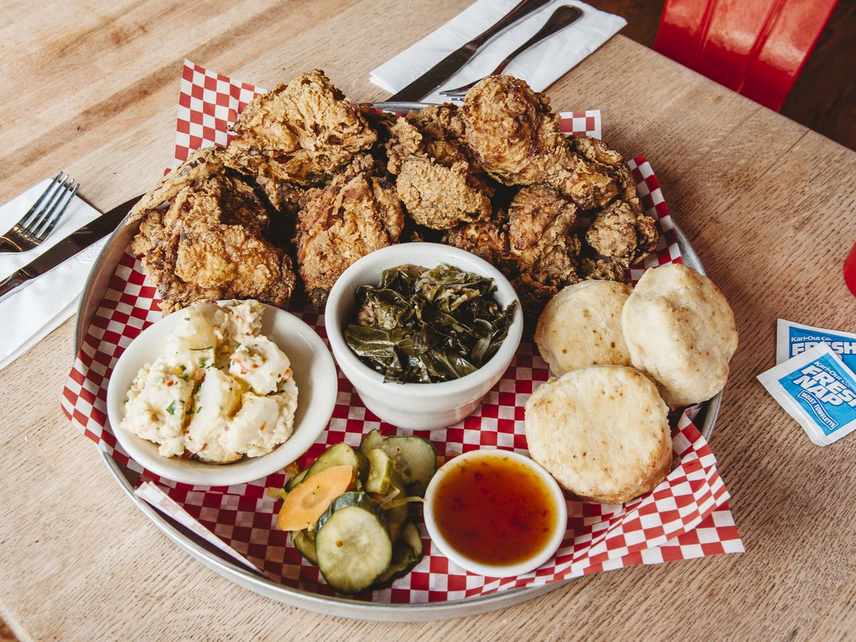 A platter of fried chicken with biscuits, collard greens, mashed potatoes, and pickles is served on a red-and-white checkered paper on a metal tray, which is on a light wooden tabletop. Moist towelettes are visible to the side of the platter.