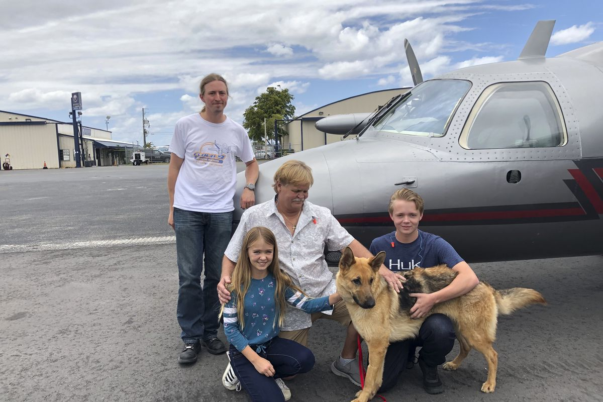In this photo provided by the Humane Society of Broward County, kneeling from left to right, Chloe, Doug and Chase Peterson greet their long-lost German Shepherd dog Cedar on Saturday, April 20, 2019, at Fort Lauderdale Executive Airport, in Fort Lauderda