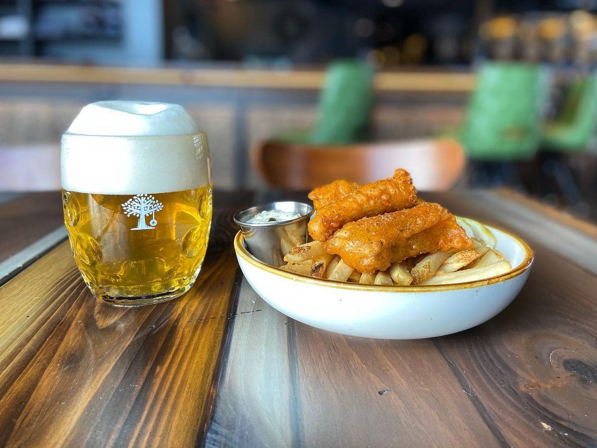 A rounded dish with fried fish on top of french fries, beside a pint of beer on a wooden table