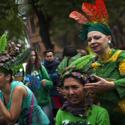 Women are seen reflected in a mirrow as they get ready to take part in a performance to celebrate the Earth Day in Barcelona, Spain, Sunday April. 22, 2012. Earth Day, a day in which people across the globe hold events to celebrate the Earth's environment and spread awareness on how to conserve its natural resources.