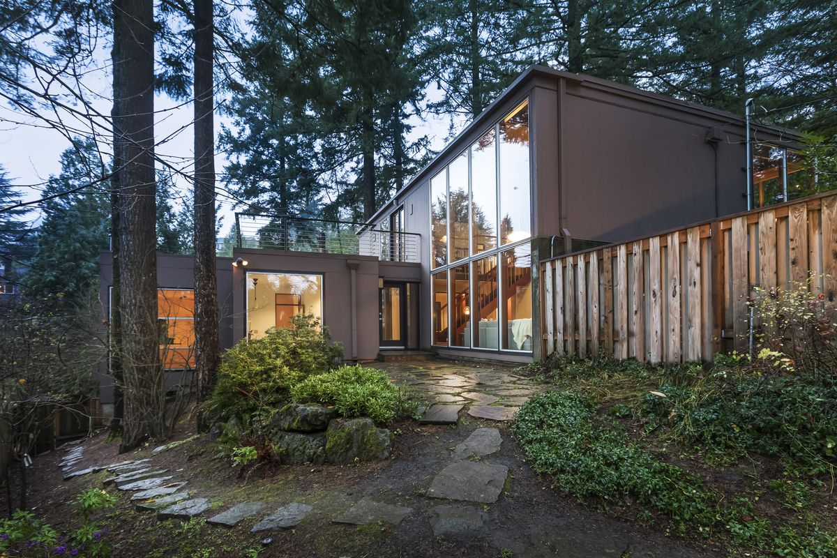 Exterior shot of blocky modern home with glass expanses set amid trees.
