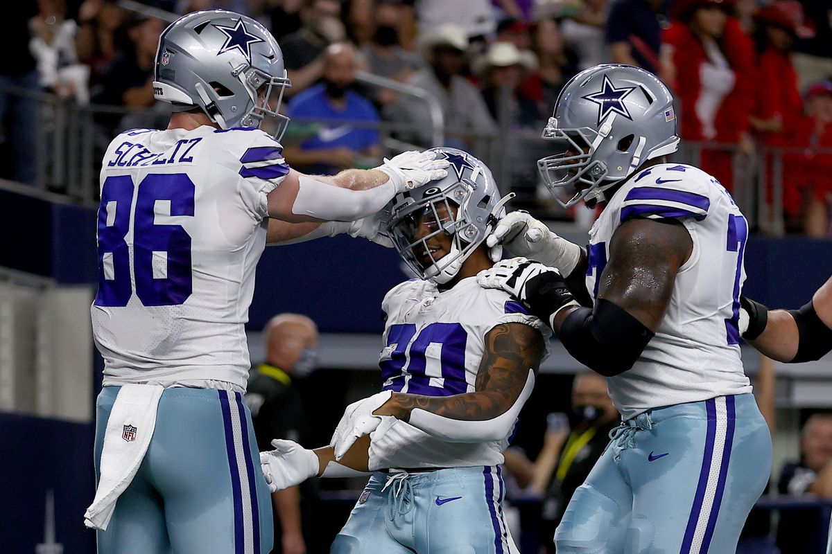 Running back Tony Pollard #20 of the Dallas Cowboys celebrates with tight end Dalton Schultz #86 of the Dallas Cowboys and offensive tackle Tyron Smith #77 of the Dallas Cowboys after scoring a touchdown against the Houston Texans in the first quarter at AT&T Stadium on August 21, 2021 in Arlington, Texas.