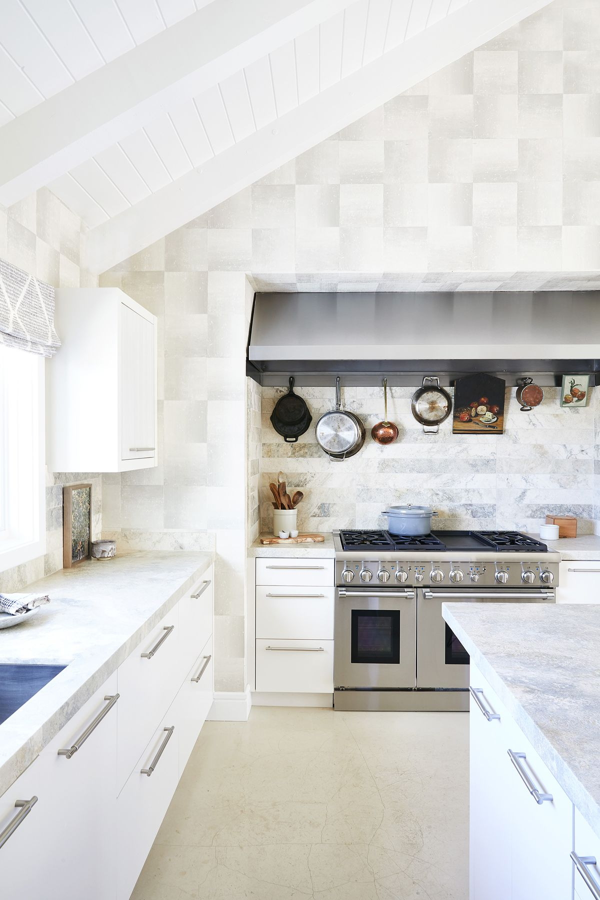 A modern kitchen with a white-painted exposed beam ceiling, gray marble countertops, white cabinets, and stainless-steel range with a stainless steel hood. Assorted pots and pans hang from the backsplash.