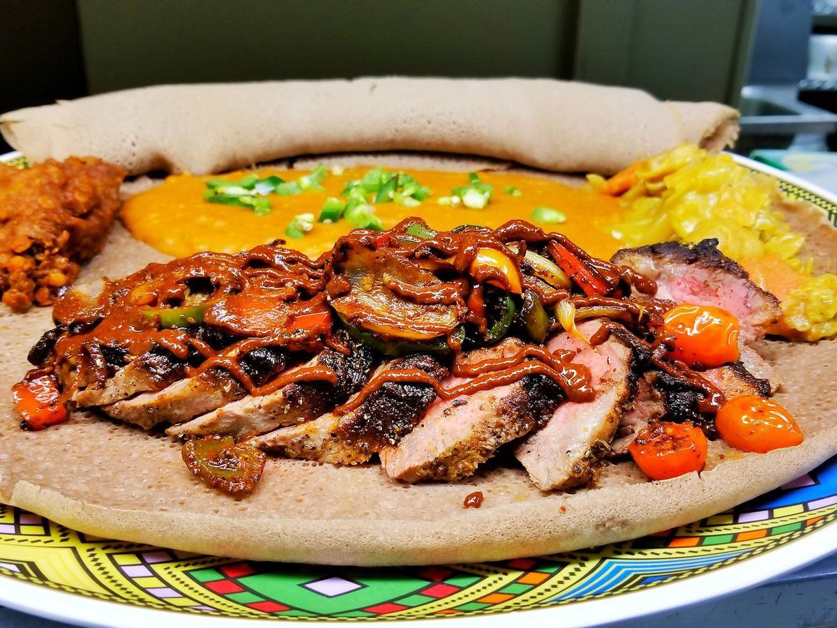 Slices of steak under roasted vegetables and awaze sauce, on a bed of injera with piles of sides