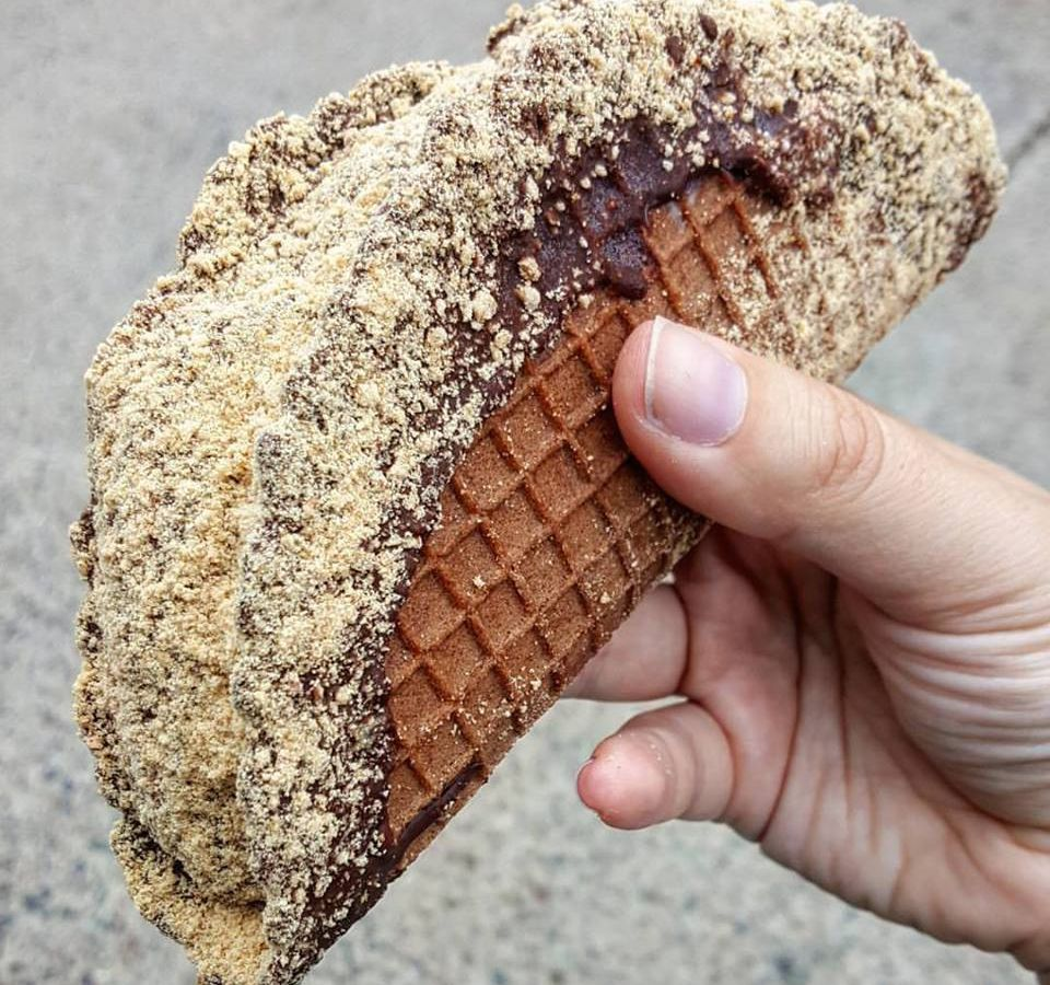 Closeup photo of a hand holding a choco taco made by an independent ice cream shop