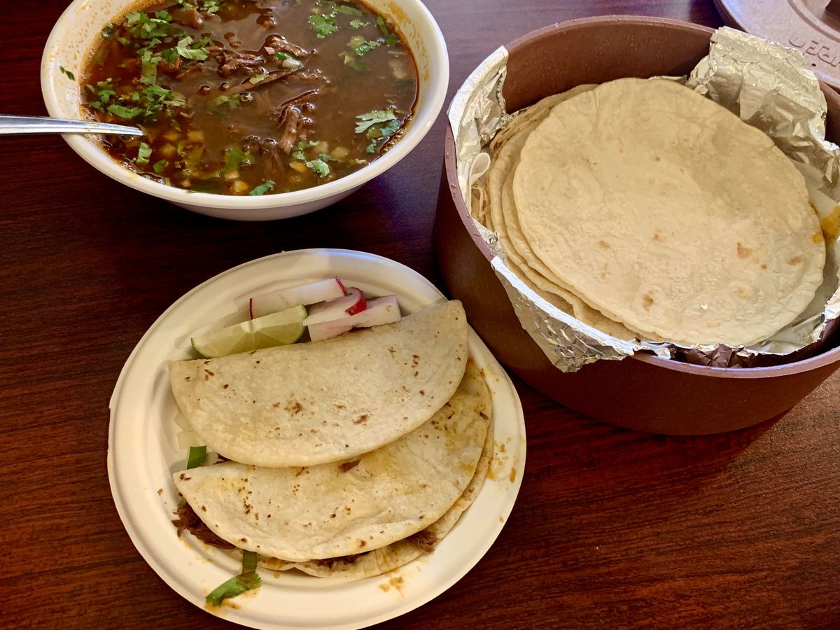 A plate of tacos with consomme and tortillas in the background