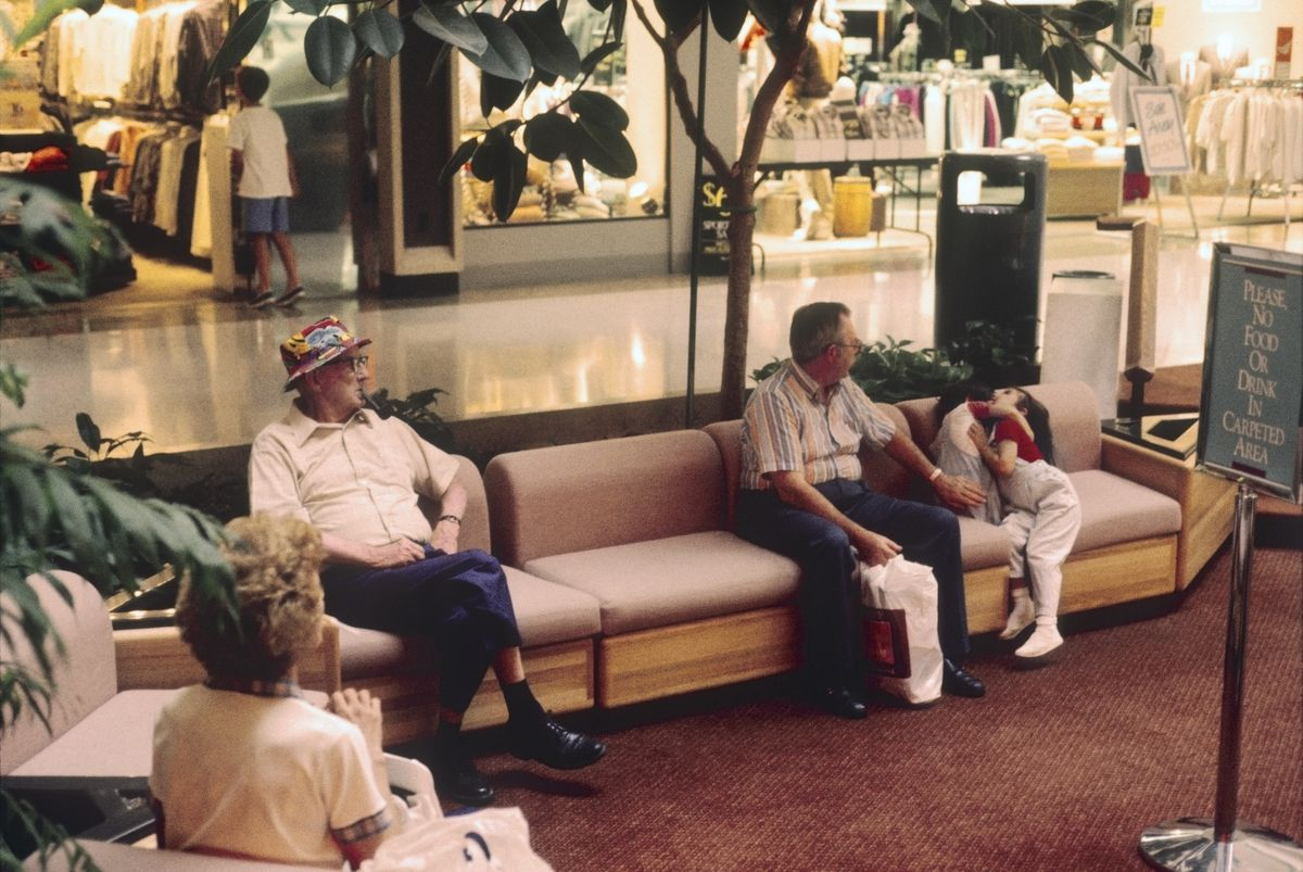 Shoppers sit on a pink bench inside a mall from a 1989 photo.