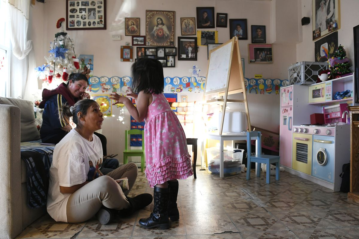 Olga Montellano, seated on floor, plays with her daughter Milagros Santos, 3, right, as friend and neighbor Berenice Morales watches.