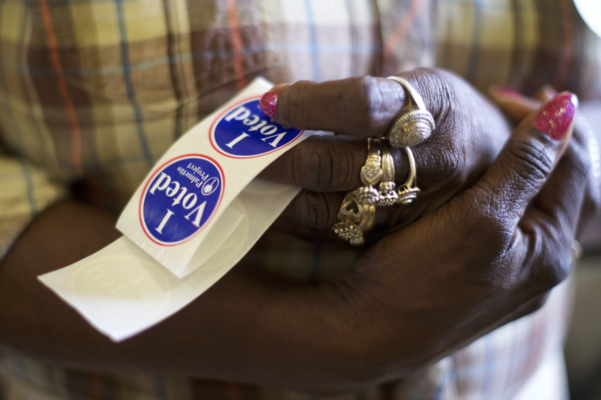African-American woman holding I Voted stickers