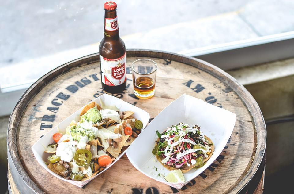 Tacos served in white paper trays and a Lone Star longneck beer on a whiskey barrel
