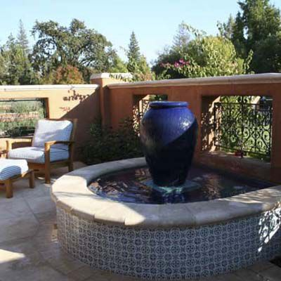 Fountain in front of masonry wall blocking a yard.